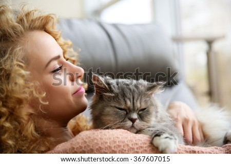Young woman and cat on sofa in the room - stock photo