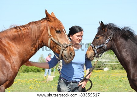 Young woman and chestnut horse with her foal - stock photo