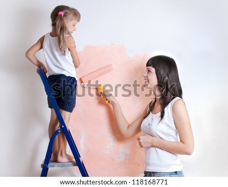 Young woman and child painting the walls, repair - stock photo