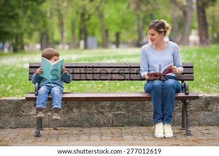 Young woman and cute little boy reading books in a park and talking - stock photo