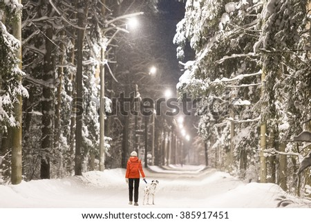 Young woman and dalmatian dog in winter forest. Trees and road covered in snow, street lights along road. - stock photo