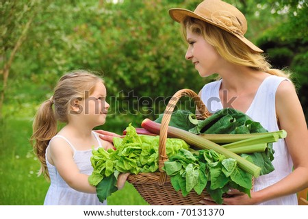Young woman and daughter with fresh vegetable