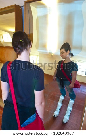 young woman and deformation mirror - stock photo