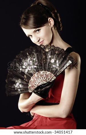 Young woman and fan over dark background