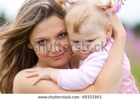 young woman and girl in meadow - stock photo