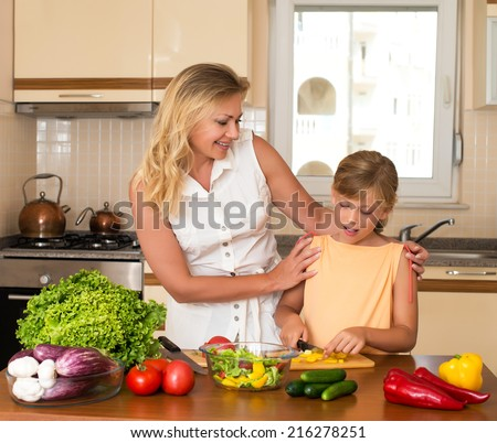 Young woman and girl making fresh vegetable salad. Healthy domestic food concept. Mother and daughter cooking together, help children to parents. - stock photo