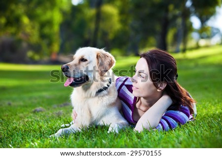 Young woman and golden retriever lying in the grass - stock photo