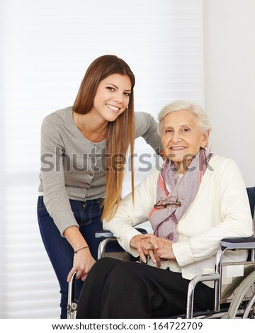 Young woman and happy senior citizen in a wheelchair - stock photo