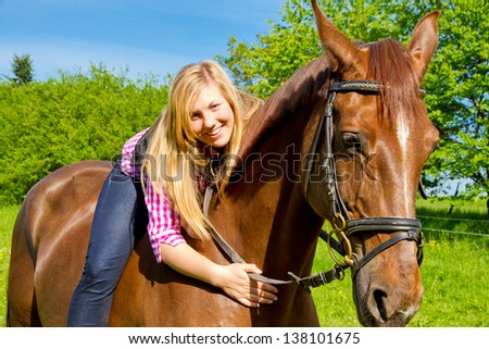 Young woman and her brown horse - stock photo