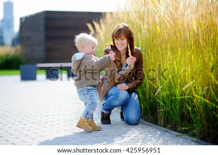 Young woman and her cute toddler son playing outdoors at sunny spring or autumn day - stock photo