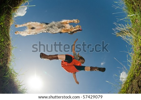 Young woman and her dog jumping over a creek, shot from below. - stock photo