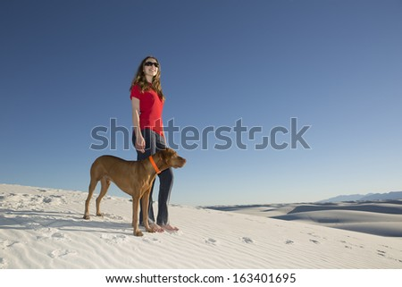 young woman and her dog standing on white sand in the desert with blue sky in the background