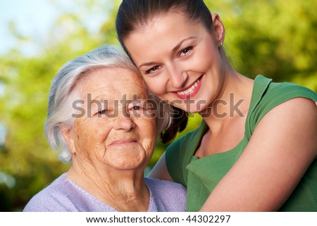 Young woman and her grandmother smiling - stock photo