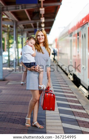 young woman and her little daughter on a railway station. Kid girl and mother waiting for train and happy about a journey. People, travel, family, lifestyle concept - stock photo