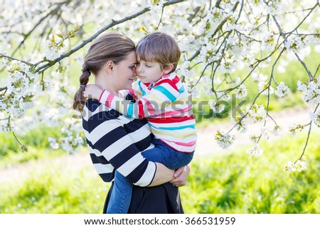 Young woman and her little son, blond kid boy hugging in blooming cherry garden in spring. Happy family celebrating mother's day. - stock photo