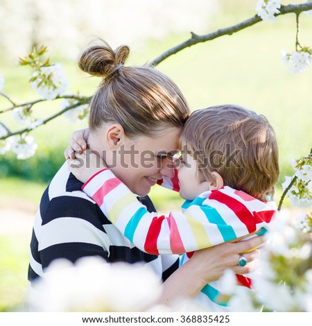 Young woman and her little son, blond kid boy in blooming cherry garden in spring. Happy family enjoying nature, togetherness and celebrating mother's day. - stock photo