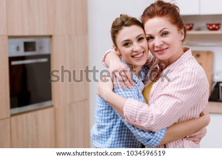 young woman and her mother embracing at kitchen