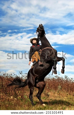 young woman and her rearing black stallion in the style of the Wild West - stock photo
