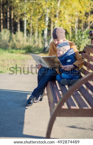 Young woman and little boy sitting on the bench in autumn Park and reading book. Family enjoying time together. Mother teaches son