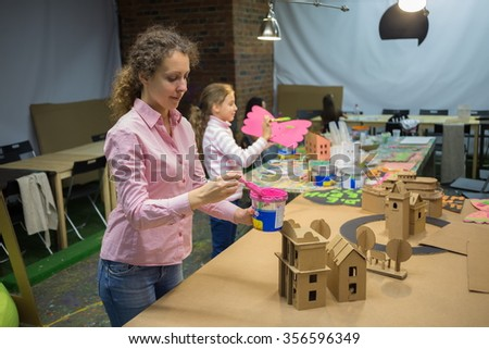Young woman and little girl are painting cardboard houses. - stock photo