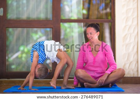 Young woman and little girl doing yoga exercise outdoor on terrace - stock photo