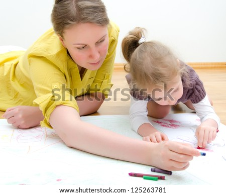 Young woman and little girl drawing together sitting on the floor - stock photo