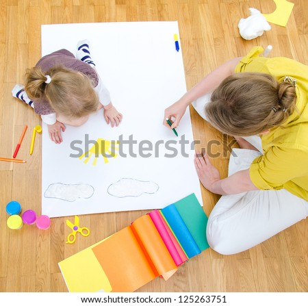 Young woman and little girl drawing together sitting on the floor. Top view - stock photo