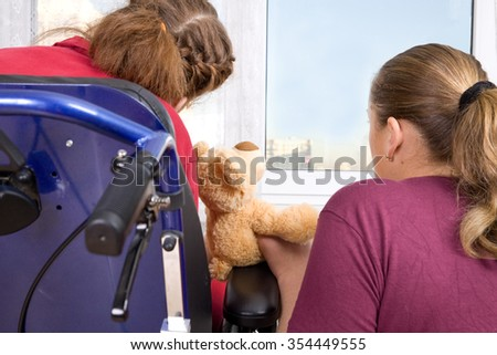 Young woman and little girl in a wheelchair near the window.