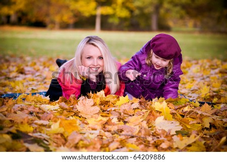 young woman and little girl playing in the autumn park