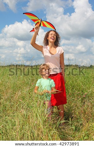 young woman and little girl plays kite on meadow