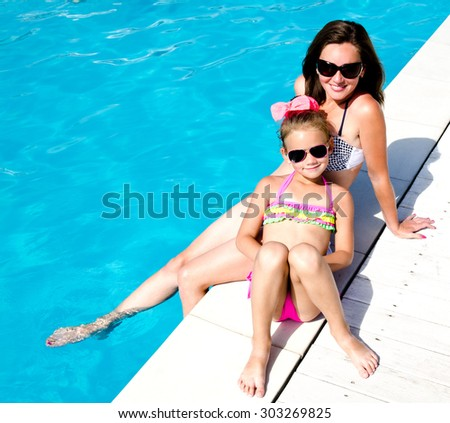 Young woman and little girl sitting near swimming pool  - stock photo