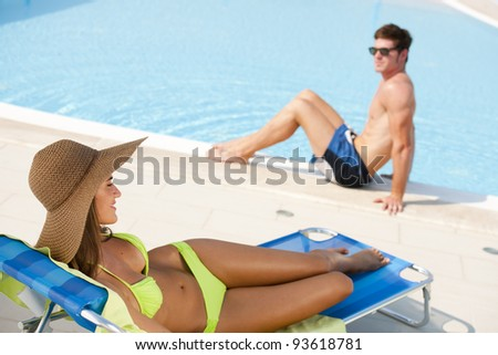 Young woman and man at swimming-pool - stock photo