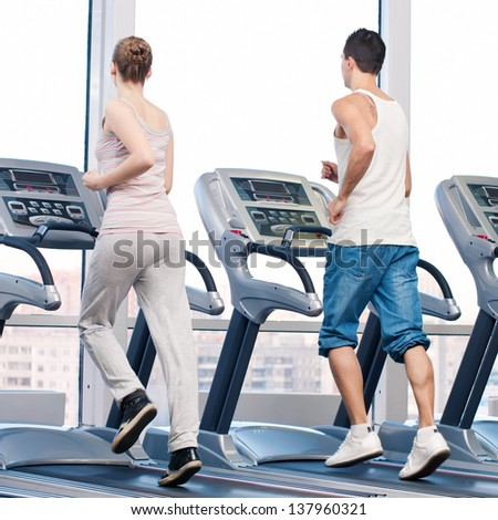 Young woman and man at the gym exercising. Run on a machine. - stock photo
