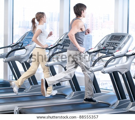 Young woman and man at the gym exercising. Run on on a machine. - stock photo