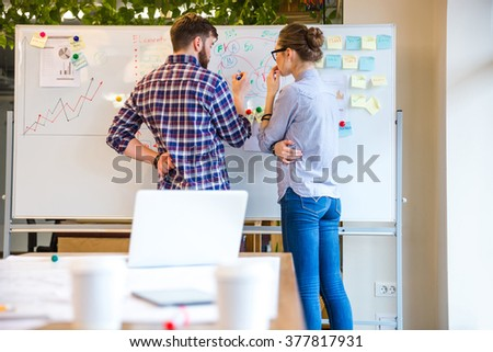 Young woman and man discussing about business strategy in office - stock photo