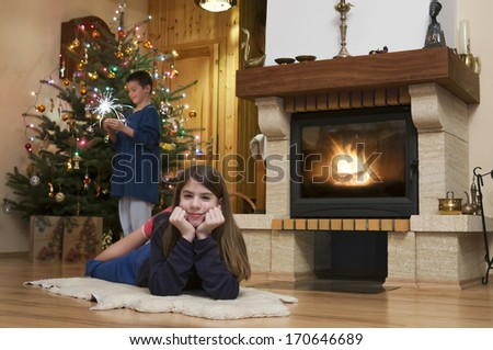 Young woman and man front of fireplace with Christmas tree in background