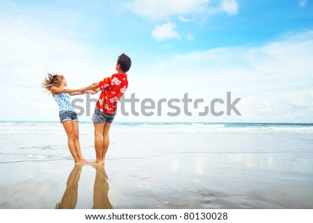 Young woman and man having fun on wet sand of a tropical sea