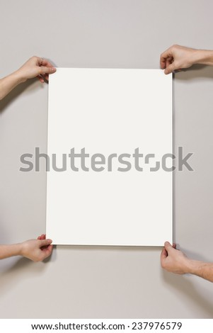 Young woman and man holding a blank poster on light beige-colored background - stock photo