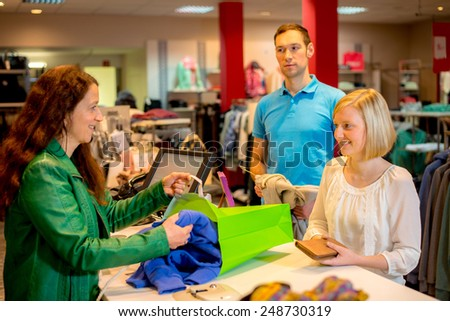 young woman and man in the clothes shop over the counter - stock photo