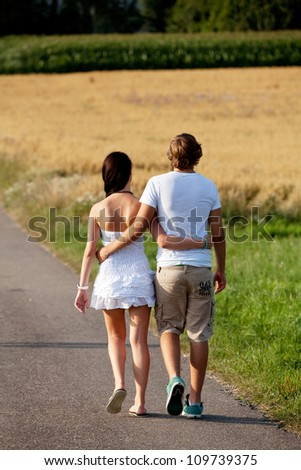 young woman and man is walking on  a road in summer outdoor happy - stock photo