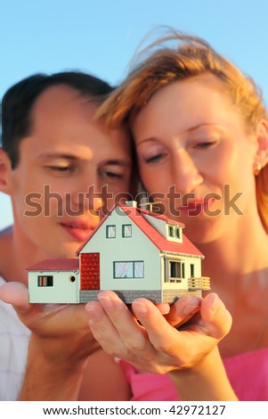 Young woman and man keeping in hands model of house - stock photo