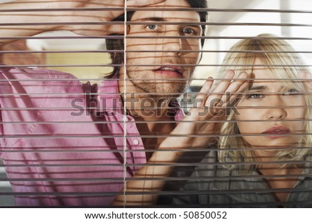 Young woman and man looking through Venetian Blinds, front view. - stock photo
