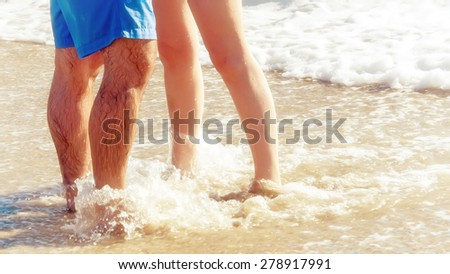 Young woman and man on the beach in the sunset - stock photo