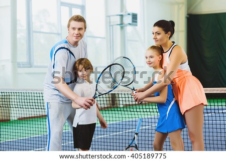 Young woman and man or coach teaching children how to play tennis on a court indoor - stock photo