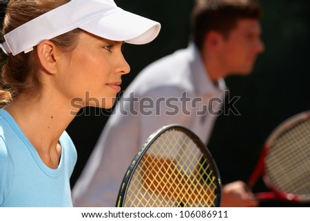 Young woman and man playing mixed doubles tennis game, side view. - stock photo