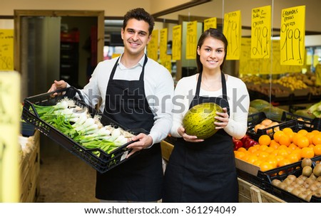 Young woman and man selling fresh grocery on market