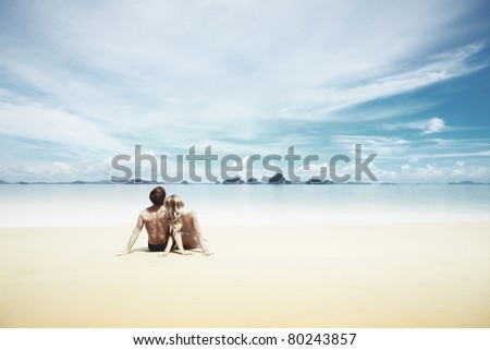 Young woman and man sitting together on a sand by sea and looking to a horizon