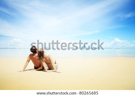 Young woman and man sitting together on a sand by sea and looking to sky - stock photo