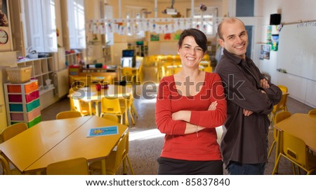 Young woman and man smiling on an elementary school classroom - stock photo