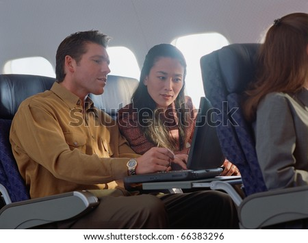 Young woman and man using laptop on airplane - stock photo